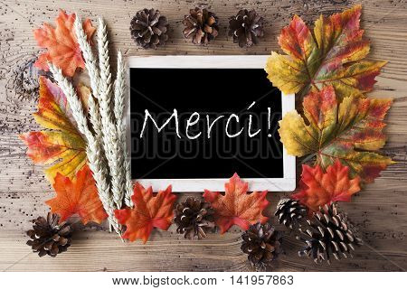 Blackboard With Autumn Or Fall Decoration. Greeting Card For Seasons Greetings. Colorful Leaves, Fir Cone And Barley On Aged Wooden Background. French Text Merci Means Thank You