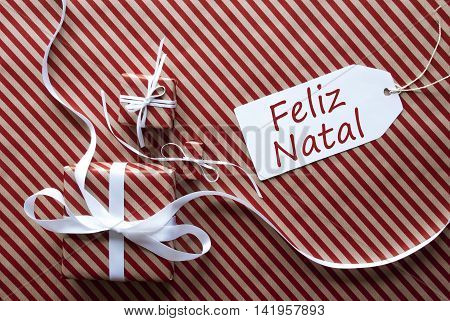 Two Gifts Or Presents With White Ribbon. Red And Brown Striped Wrapping Paper. Christmas Or Greeting Card. Label With Portuguese Text Feliz Natal Means Merry Christmas