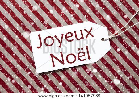 One Label On A Red And Brown Striped Wrapping Paper. Textured Background With Snowflakes. Tag With Ribbon. French Text Joyeux Noel Means Merry Christmas
