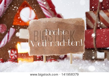Gingerbread House In Snowy Scenery As Christmas Decoration. Sleigh With Christmas Gifts Or Presents And Snowflakes. Label With German Text Frohe Weihnachten Means Merry Christmas