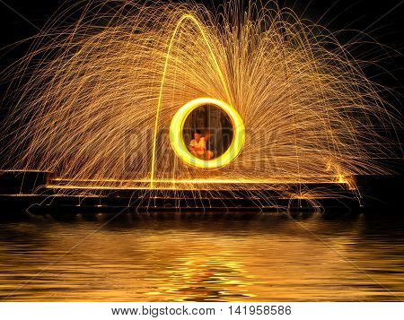 Hot Golden Sparks Flying From Man Spinning Burning Steel Wool On The Stair Near River With Water Ref