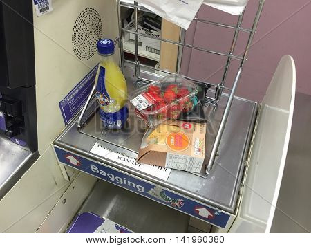 LONDON - AUGUST 9: Products placed in the bagging area scales by a customer at a self service checkout in Tesco in Hampstead on August 9, 2016 in London, UK.