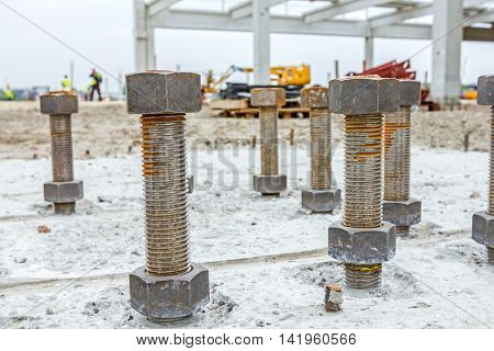 Close up the anchor bolts in concrete base of new edifice with reinforcement at building site.