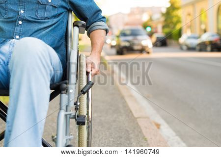 Paralyzed man using his wheelchair in a city