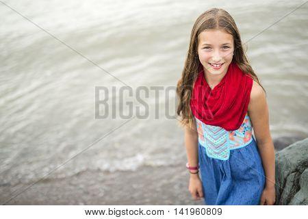 A Girl enjoying the rain and having fun outside on the beach on a gray rainy