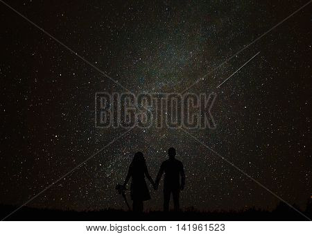 Silhouette of man on a background of stars. Girl desires guess looking at the stars.