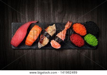Sushi on black stone slate plate black wooden background