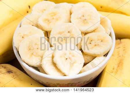 Prata Banana slices into a bowl over a wooden table