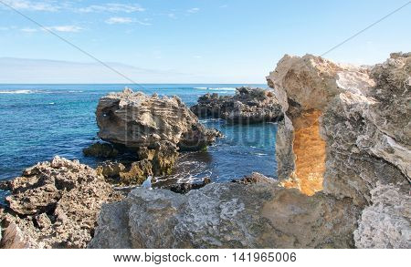 Rugged coastal limestone formations and large ocean rocks in the Indian Ocean waters at Point Peron in Rockingham, Western Australia