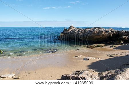 Remote cove with sandy beach, limestone outcropping and turquoise Indian Ocean waters at Point Peron in Rockingham, Western Australia