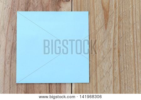 blue paper note on old brown wood background for design and input text.