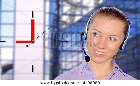 Woman wearing headset in office; could be receptionist and clock