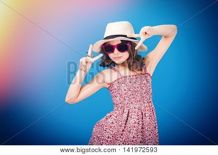 Cute playful little girl in hat, sundress and sunglasses showing victory sign with both hands over blue background
