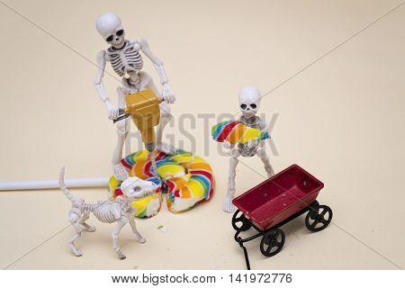 Skeleton breaking lollipop into pieces for the skeleton kid