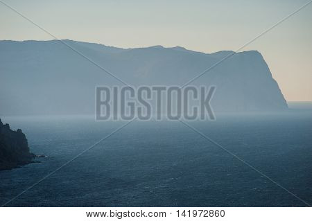 landscape of sea and mountains in the mist