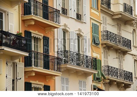facades of houses with windows and balconies with magnificent openwork lattices in Monaco