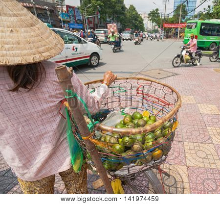 Ho Chi Minh City, Vietnam - October 12, 2013: Woman stands at busy intersection back on holding her basket of fresh green skinned oranges hoping to sell some and earn a living Vietnam, Saigon, Ho Chi Min City