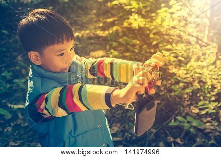 Happy asian boy with camera at national park . Child relaxing outdoors with bright sunlight at the day time travel on vacation. Vintage tone.