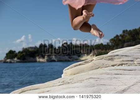 Sexy Legs of a young woman jumping from a white rock into the sea