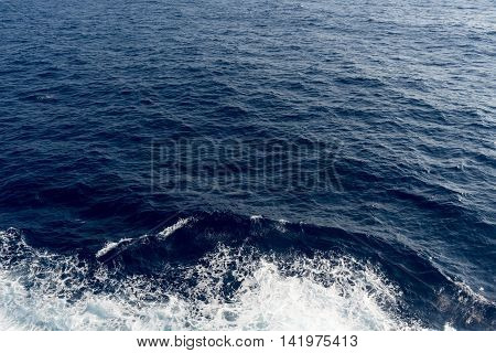 Deep blue Sea or ocean water surface background with ripples and waves