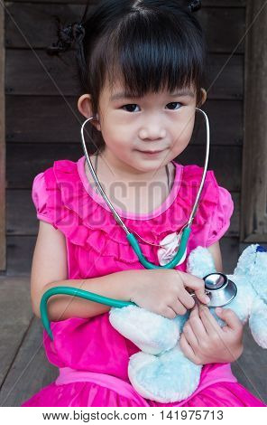 Closeup adorable asian child playing doctor or nurse with plush toy bear at home. Happy girl listens a stethoscope to toy. Playful girl role playing.