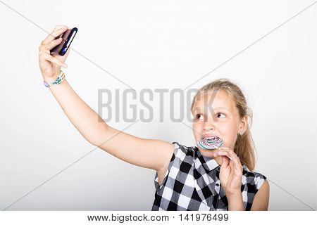 Portrait of happy beautiful young girl makes salfie, expresses different emotion. pretty teenager girl with big circle lollipop