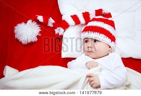 Sleepy baby on red blanket in knitted hat. Cute child sleeping in christmas cap