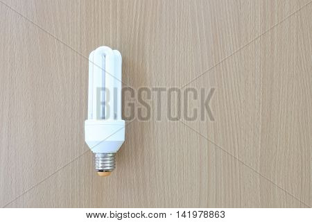 White Compact Fluorescent Lamps rests on a wooden floor.