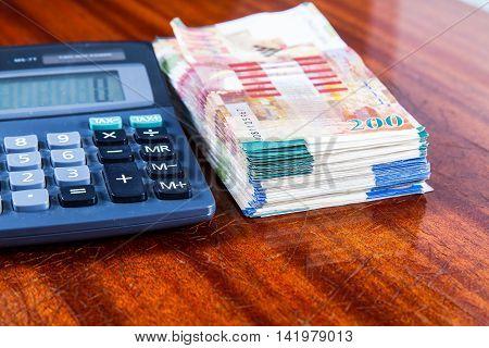 Israeli New Sheqel and calculator on wood background .