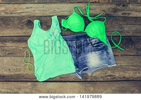 Summer women's clothing: tank top, bathing suit, denim shorts. Toned image.