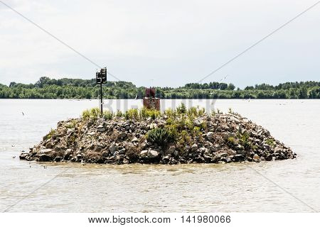 Small island of stones with flying and nesting gulls on the Danube river. Natural scene. Beauty in nature.