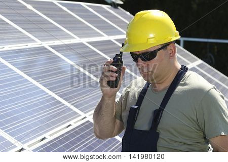 Green energy solar panel and worker with walkie talkie