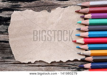 Closeup Color pencils concatenation on brown paper and old wooden background for concept design of education.