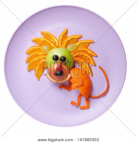 Sneaky lion made of orange and apple on plate