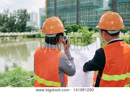 Contractor using walkie-talkie when working on construction site