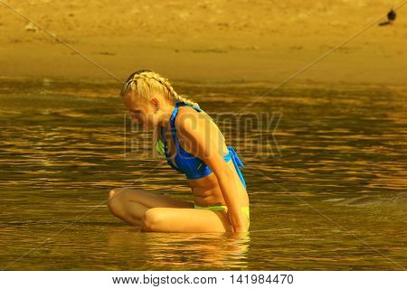 girl in swimsuit sits and basks in the sun on the sandy shallow water on the beach and enthusiastically looking at the water