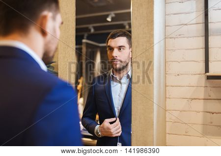 sale, shopping, fashion, style and people concept - elegant young man choosing and trying jacket on and looking to mirror in mall or clothing store