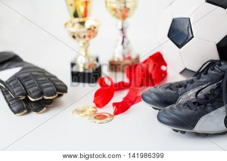 sport, achievement, championship and success concept - close up of soccer ball, football boots and goalkeeper gloves with golden medals and cups