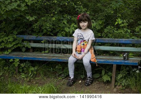 smiley little girl sitting at the wooden banch in the forest
