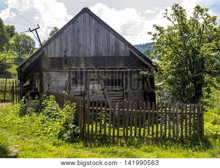 old grey wooden rustic barn and wooden fence at front