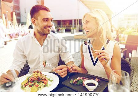love, date, people, holidays and relations concept - happy couple eating salad for dinner at cafe or restaurant terrace