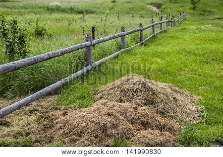 rural scene with wooden fence and armful of straw