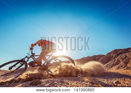 Man braking the bicycle with lot of dust  in the desert at sunny day