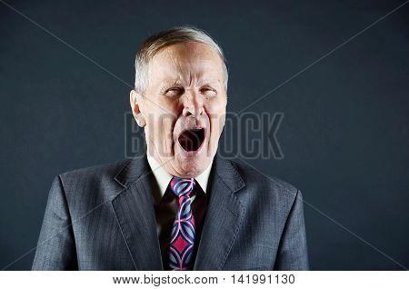 Closeup senior man  portraitwith a big yawn, isolated on black background