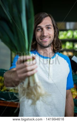 Portrait of man holding leafy vegetable while shopping in supermarket