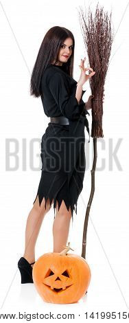 Young witch with broom and halloween gourd isolated on white background