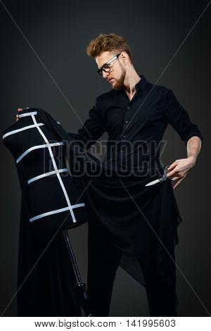 Fashion designer working with dummy at studio. Black background.