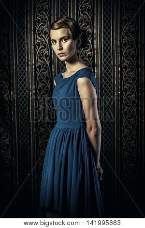 Gorgeous young woman in elegant evening dress standing by a vintage wallpaper. Fashion shot. Retro hairstyle.