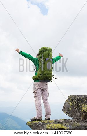Hiker with backpack standing on top of a mountain . Happy hiker winning reaching life goal success freedom and happiness achievement in mountains. Thumbs-up.