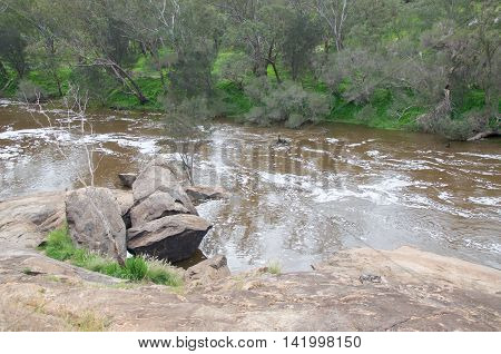 Elevated view over the Swan River downstream from the bell rapids with foamy flowing waters in the Swan Valley in Western Australia.